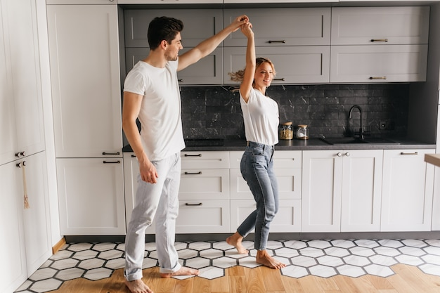Stylish girl in jeans dancing with husband in morning. indoor portrait of relaxed young people having fun in kitchen.
