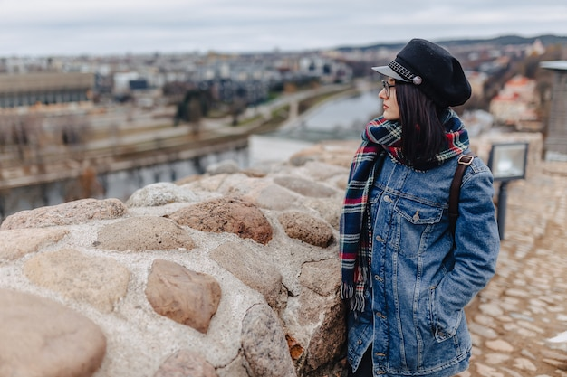 Stylish girl in jeans jacket walk at the vilnius background