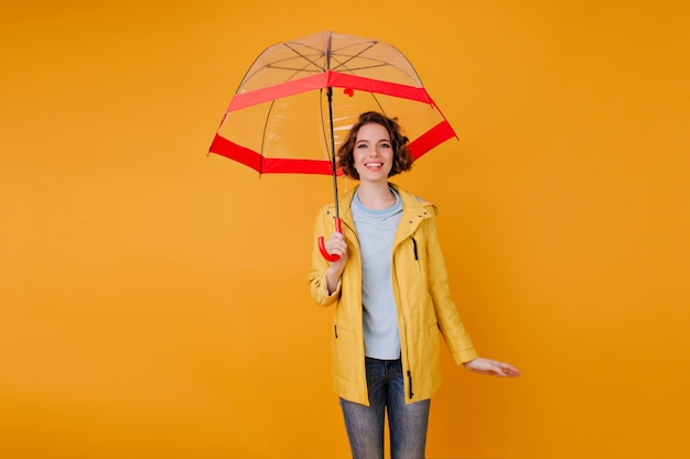Stylish girl in jeans and raincoat standing under cute umbrella. indoor portrait of romantic young woman with curly hairstyle holding parasol on orange wall.