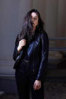 Stylish girl in a leather jacket and evening makeup, standing on the street of the city at night