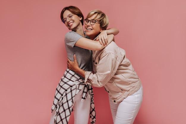 Ragazza alla moda in abiti scozzesi leggeri sorridendo e abbracciando la donna anziana con gli occhiali una giacca beige fresca su sfondo rosa isolato.