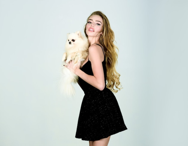 Stylish girl in little black dress with dog in hands. woman with pet puppy. beautiful woman with pomeranian spitz. fashion animal. canine breed. girl holds little dog. isolated.