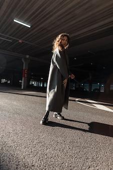 햇빛과 그늘에서 도시를 걷는 세련된 긴 코트에 곱슬 머리를 가진 세련된 소녀 모델. 어반 캐주얼 여성 패션과 스타일