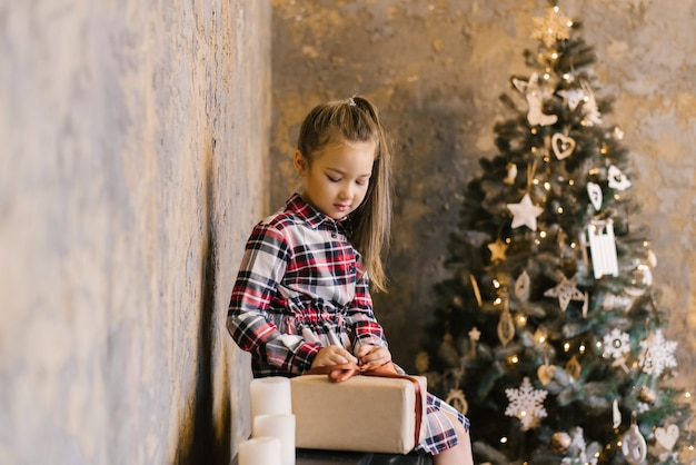 Stylish girl in a plaid dress opens her christmas gift