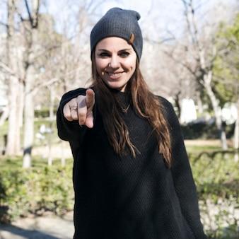 Stylish girl pointing at camera