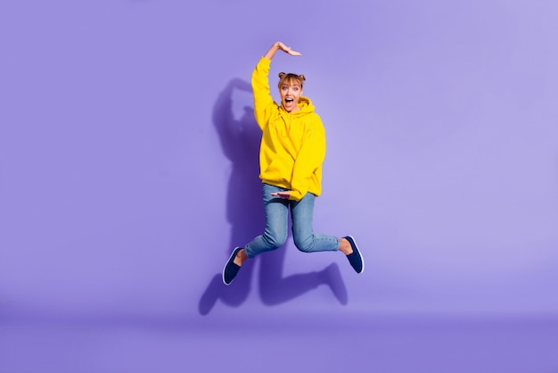 Stylish girl posing against the purple wall