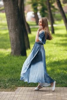 日当たりの良い春の公園でドレスでポーズをとるスタイリッシュな女の子。夏の美しい少女の明るく幸せな肖像画。