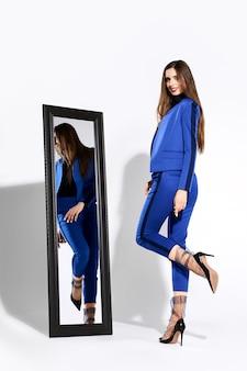 팬츠 수트와 얇은 명주 그물 양말 거울 근처에서 포즈 세련 된 소녀