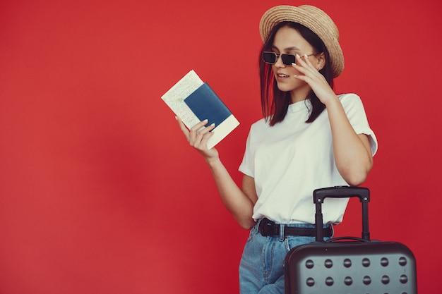 Стильная девушка позирует с туристическим снаряжением на красной стене