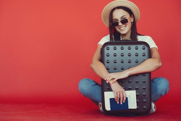 빨간 벽에 여행 장비와 함께 포즈를 취하는 세련 된 소녀