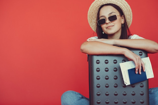 Stylish girl posing with travel equipment on a red wall