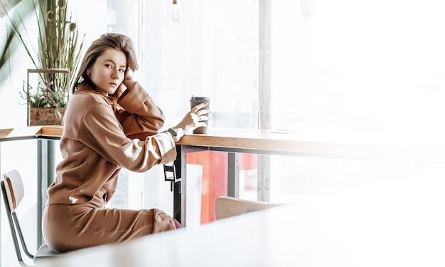 Стильная девушка сидит в кафе и пьет кофе. кофе с собой в картонной чашке. женщина с рыжими волосами в бежевом теплом костюме в уютной атмосфере. современный интерьер. спокойное и приятное времяпровождение