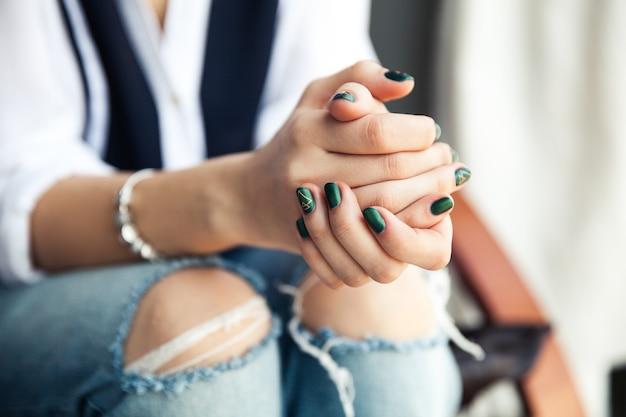 Стильная девушка сидит в рваных джинсах и современном зеленом лаке для ногтей, часах, браслете. мода, образ жизни, красота, одежда. и