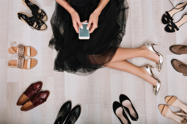 Стильная девушка, сидя на полу в гримерке со смартфоном в руках, пишет сообщение в окружении разнообразной обуви. она одета в черную юбку, на ногах роскошные серебряные туфли.