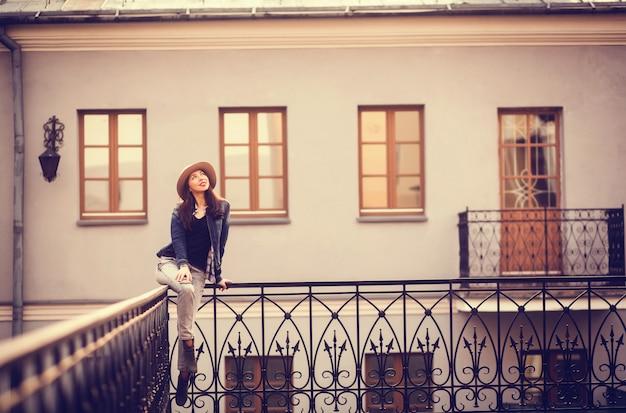 Stylish girl sitting on the railing