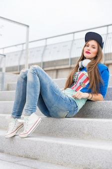 Stylish girl sitting on steps