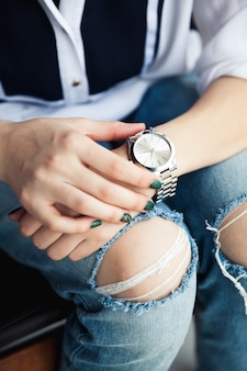 Stylish girl sitting in torn jeans and green modern manicure, bridge silver watch, bracelet. fashion, lifestyle, beauty, apparel. and