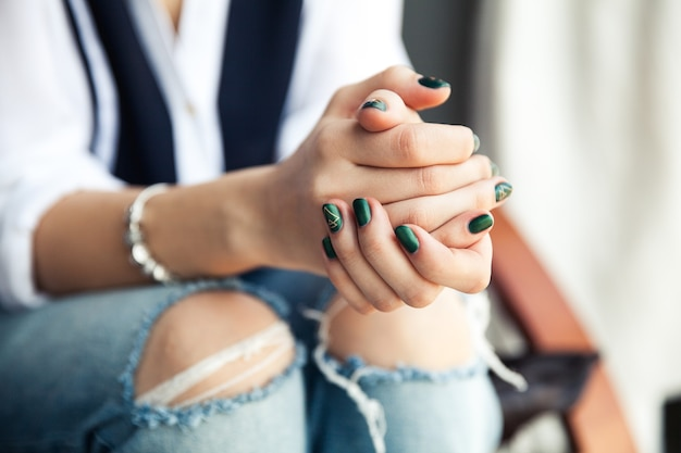 Stylish girl sitting in torn jeans and modern green nail polish, watch, bracelet. fashion, lifestyle, beauty, clothing. and