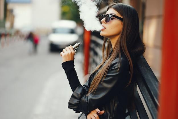 그녀는 도시를 걷는 동안 전자 담배를 피우는 세련된 소녀