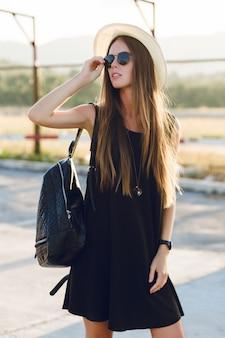 短い黒のドレス、麦わら帽子、黒の眼鏡、黒のバックパックを身に着けている道の近くに立っているスタイリッシュな女の子。彼女は夕日の暖かい光線の中で微笑んでいます。彼女はサングラスを手で触れます