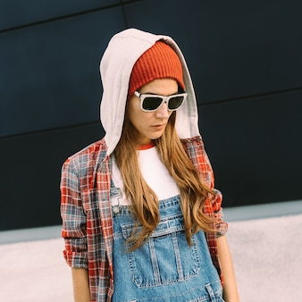 Stylish girl student. autumn urban denim overalls and red accessories.