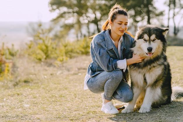 Ragazza alla moda in un campo soleggiato con un cane