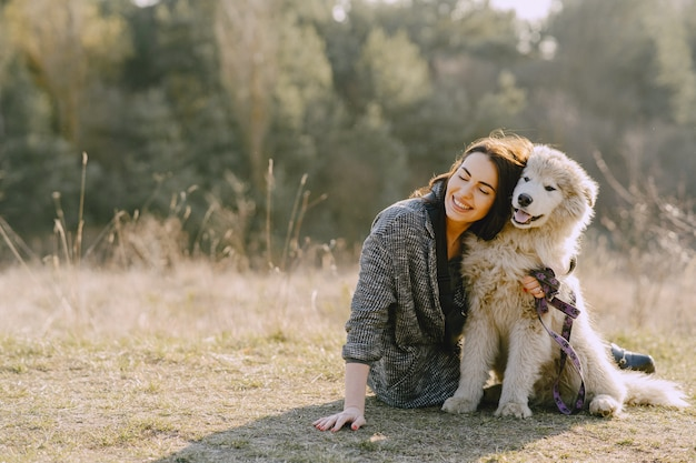 Stylish girl in a sunny field with a dog