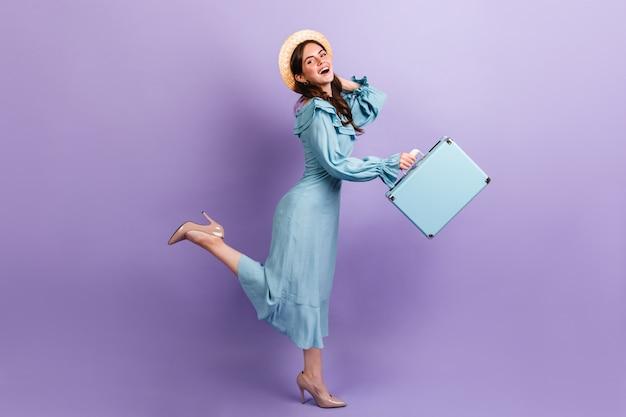 세련된 소녀 여행자는 라일락 벽에서 실행됩니다. 모자와 발 뒤꿈치의 모델은 가방을 유지합니다.