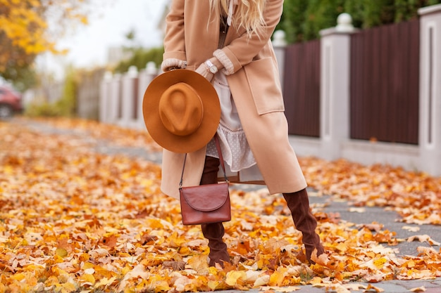 Stylish girl walks in autumn park in a beige coat and hat