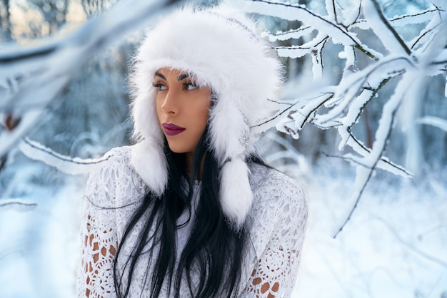 Stylish girl in warm hat in winter forest.