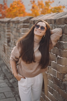 Стильная девушка в темных очках посещает великую китайскую стену