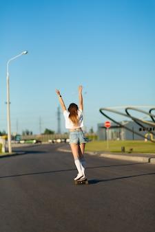 Stylish girl in white stockings enjoy ride on longboard put hands up