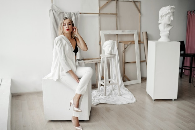 Stylish girl in a white suit sits on a white cube in a gallery