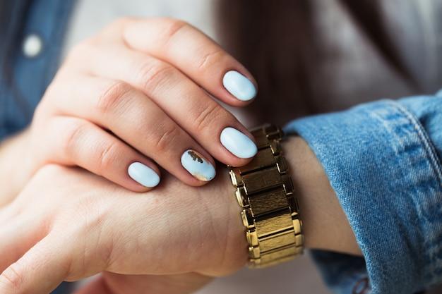 Стильная девушка с синим маникюром и золотыми часами.