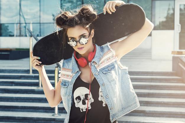 Стильная девушка со скейтбордом