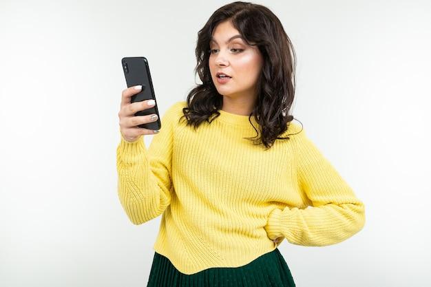 白いスタジオの背景に憤慨している手にスマートフォンを持つスタイリッシュな女の子。