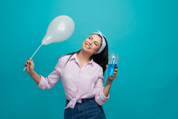 Стильная девушка с шаром и газированных напитков позирует.