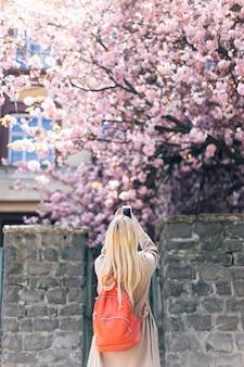 Стильная девушка с длинными светлыми волосами фотографировать под цветущее дерево.