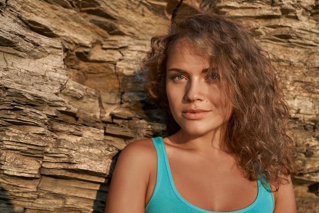 岩の背景に巻き毛のスタイリッシュな女の子