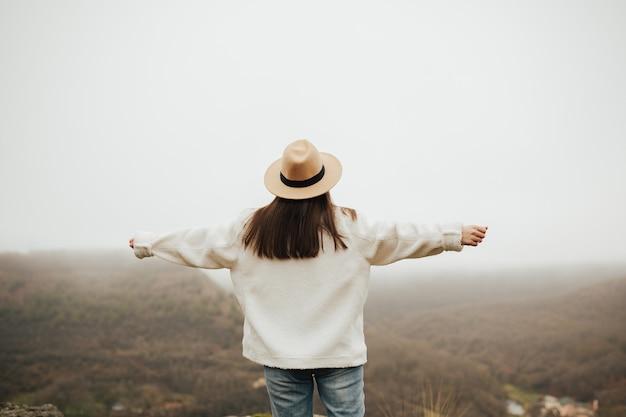 腕を広げて美しい風景を楽しむ帽子をかぶったスタイリッシュな女の子、背面図。