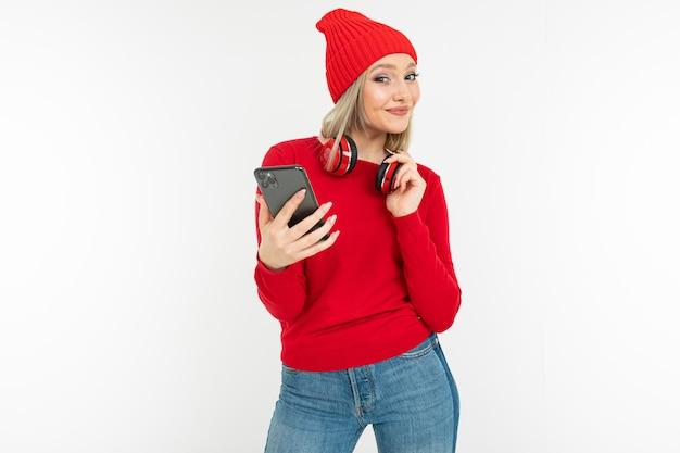 Стильная девушка с наушниками на шее делает селфи на телефоне на белом фоне с копией пространства