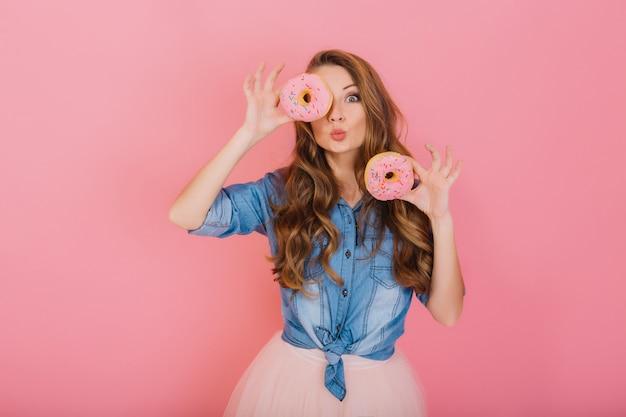 Elegante ragazza con lunghi capelli ricci posa positivamente, tenendo ciambelle rosa fresche con polvere pronta per gustare i dolci ritratto di giovane donna attraente in camicia di jeans retrò divertendosi con dolci