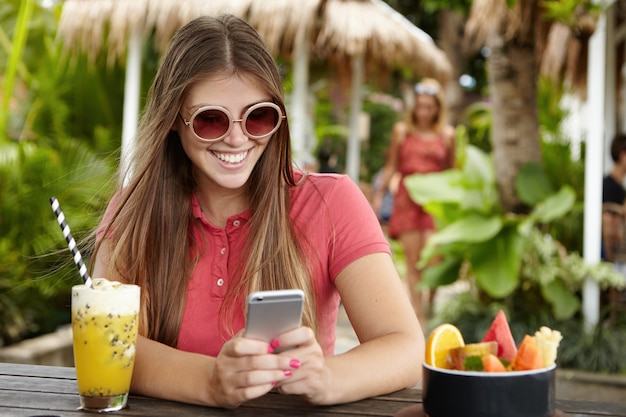 Stylish girl with long hair messaging friends via social networks on her cell phone