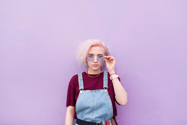 Стильная девушка с розовыми волосами и солнцезащитными очками имеет фиолетовый фон и смотрит в камеру