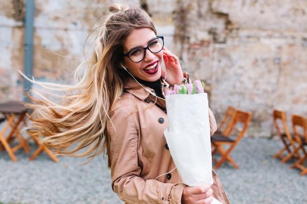 Стильная девушка с красивой прической в очках дурачится и смеется, неся букет тюльпанов. прелестная молодая женщина в бежевой куртке с светлыми струящимися волосами, улыбаясь на фоне размытия.