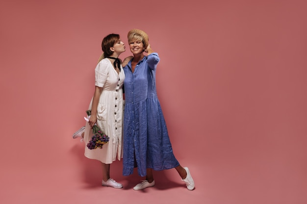 Stylish girl with short hair in white dress holding wildflowers and kissing on cheek to blonde old lady in blue clothes and hat on pink backdrop.