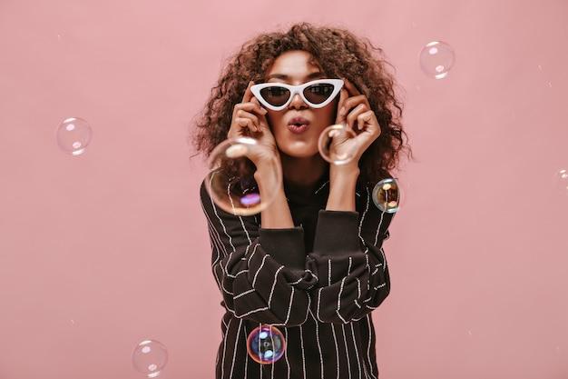 Ragazza alla moda con una breve acconciatura ondulata in abito nero a righe che soffia bacio, tiene in mano occhiali da sole bianchi e posa con una bolla sul muro rosa..