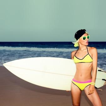 ビーチで白いサーフボードを持つスタイリッシュな女の子