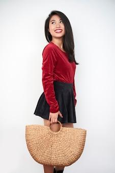 Стильная девушка с тканой сумкой