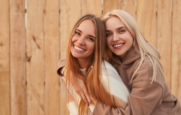 Stylish girlfriends having fun and hugging